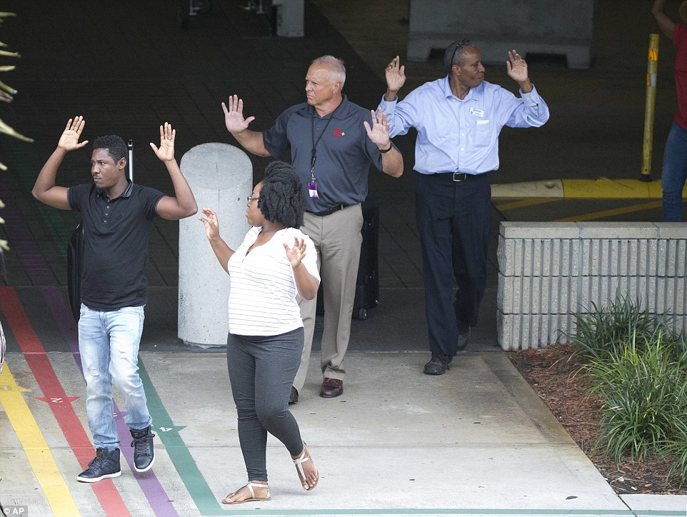 A group of people are seen walking out of a parking garage with their hands in the air after the shooting