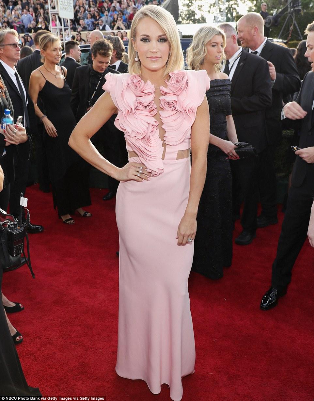 Ruffles em babados: Carrie Underwood parecia estar sendo esmagado sob uma massa de rosas de tecido
