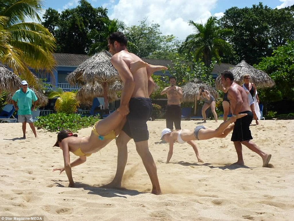 In the photos Miss Markle can be seen taking part in a wheelbarrow race with wedding guests on the Jamaican beach