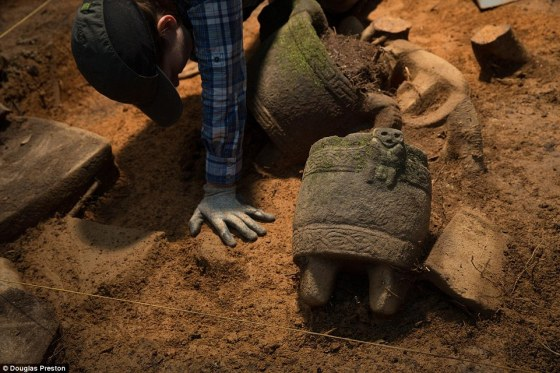 Excavation: Archaeologist Anna Cohen excavates stone vessels, one of which has a figure of unknown origin. Theories include the possibility that is a corpse bound for burial, a captive waiting sacrifice, or a half-monkey-half-human deity