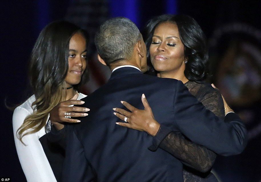 Barack embraces his wife Michelle after paying tribute to her and his daughters Malia, pictured, and Sasha