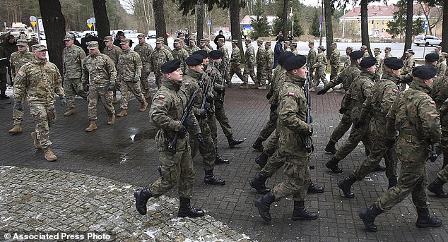 US (left) and Polish soldiers (right) march in a procession during the official welcome ceremony in Zagan, Poland, on Thursday