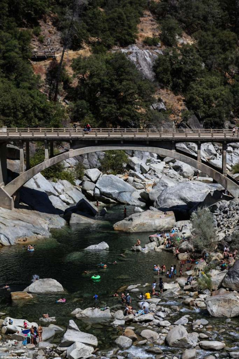 People swim under theSouth Yuba River Bridge in Nevada City, California in September 2016, as many rocks are exposed due to the low water levels