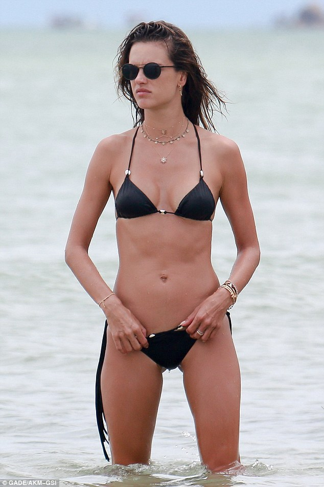 Beach babe: Alessandra Ambrosio, 35, showed once again just how good she looks in a bikini when she went for a dip in Canasvieiras, on Sunday, in a skimpy black two-piece