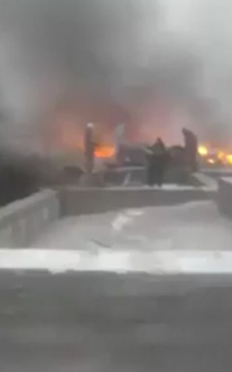 Dramatic video shows how buildings and plane wreckage were still on fire when rescuers descended on the scene after the crash this morning