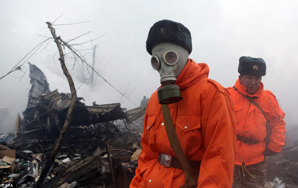 Rescue workers wore gas masks as they picked through the wreckage in the aftermath of the crash this morning