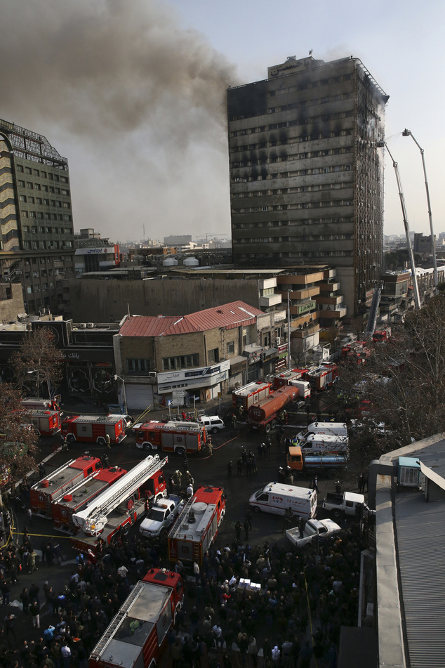 Smoke rises up from the Plasco building where firefighters work to extinguish fire in central Tehran, Iran, Thursday, Jan. 19, 2017. The high-rise building w...