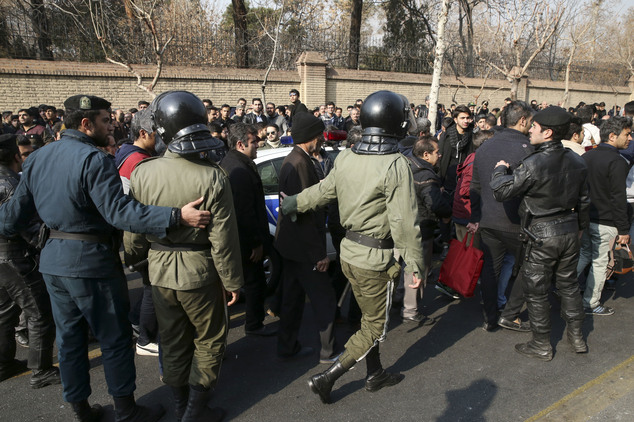 Police officers direct people in front of the Plasco building engulfed by a fire, in central Tehran, Iran, Thursday, Jan. 19, 2017. A high-rise building in T...
