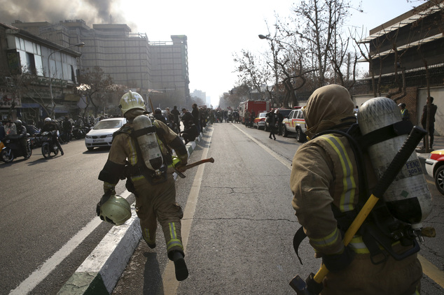 Iranian firefighters run towards the Plasco building engulfed by fire in central Tehran, Iran, Thursday, Jan. 19, 2017. The high-rise building engulfed by a ...