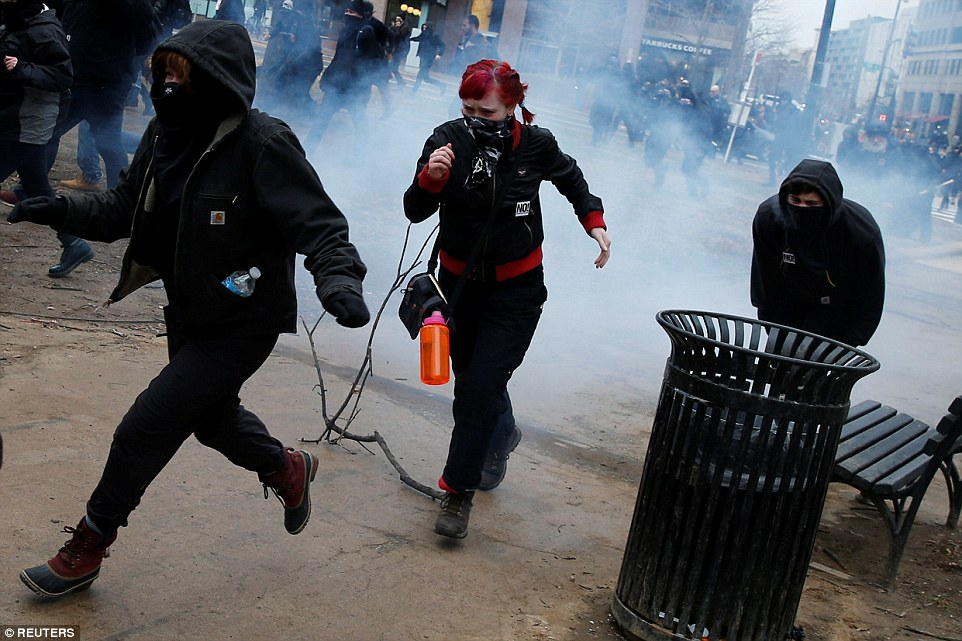 Activists run after being hit by a stun grenade while protesting against Trump on the sidelines of the inauguration
