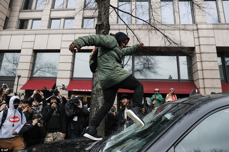 A young male rioter kicked in a car's windshield as fellow protesters watched on