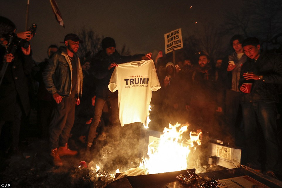 A protester burns one of Trump's Make America Great t-shirt just hours after he was sworn in as president