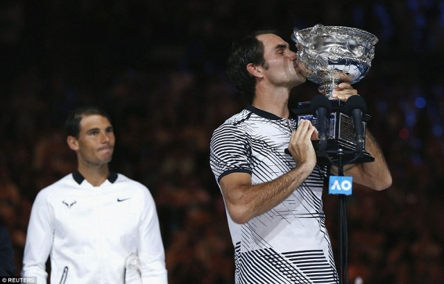Roger Federer lifts the Australian Open trophy for the fifth time in his career after beating Rafael Nadal across five sets
