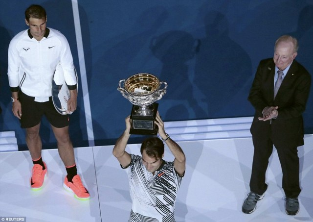 Rod Laver (right) applauds after handing the trophy over the Federer while Nadal holds his runner's up plate