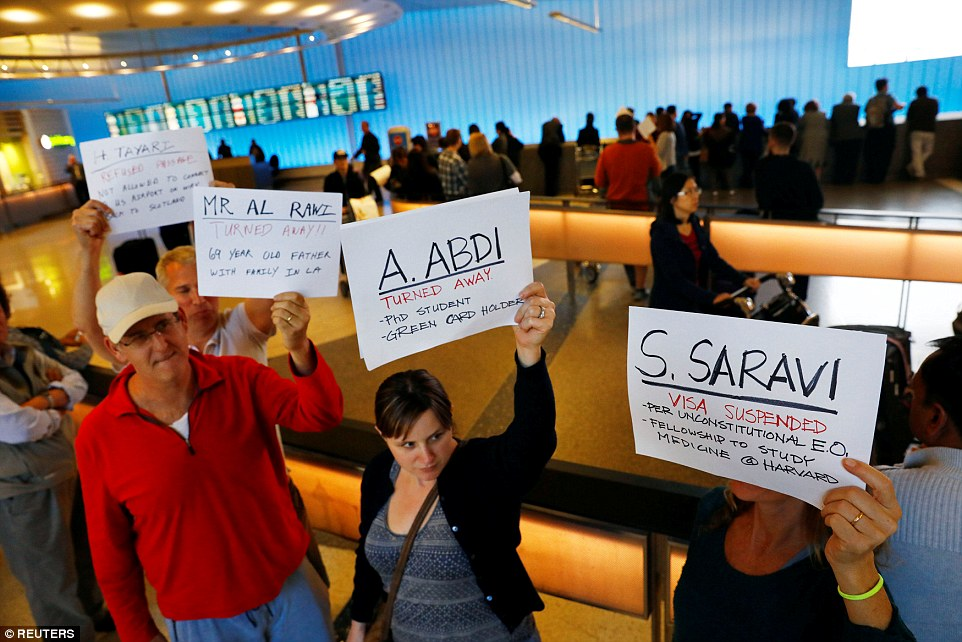 People held signs with the names of people detained and denied entry at Los Angeles International Airport on Saturday