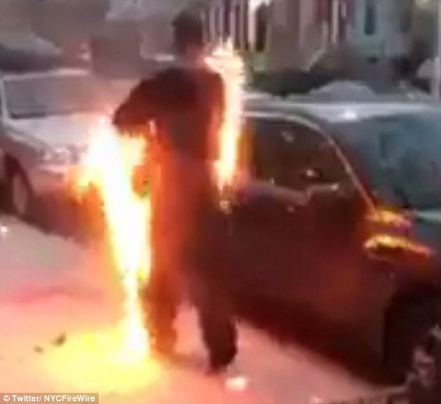 Shocking footage shows the burning man standing on a sidewalk near parked cars and calmly removing his coat