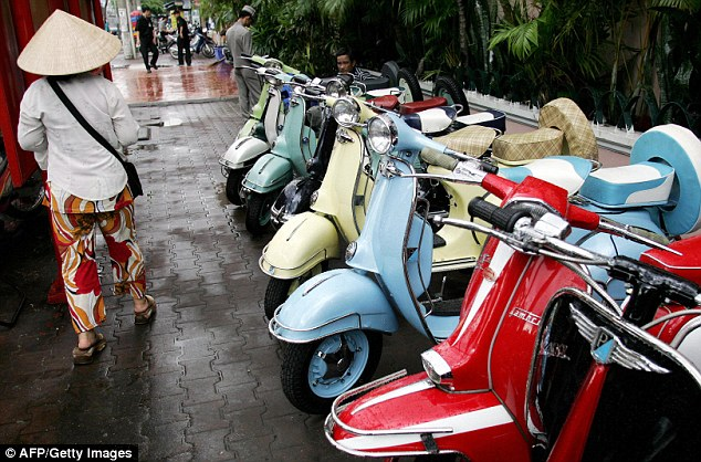 Vespa is better known for its iconic scooters. Here, a woman walks past a row of repaired old scooters displayed for sale along a street in Ho Chi Minh, Vietnam