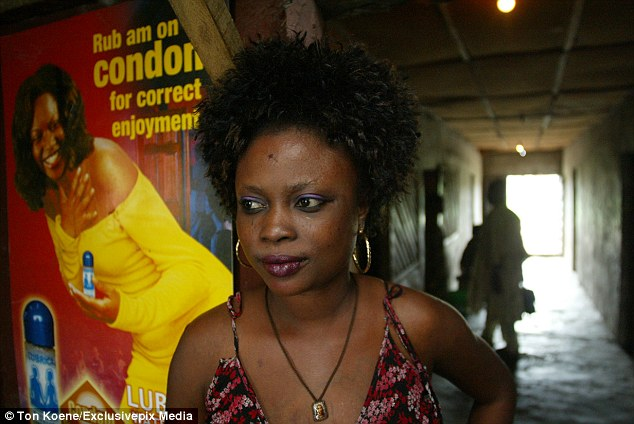 A woman stands in front of an advertisement encouraging condom use in Lagos, Nigeria