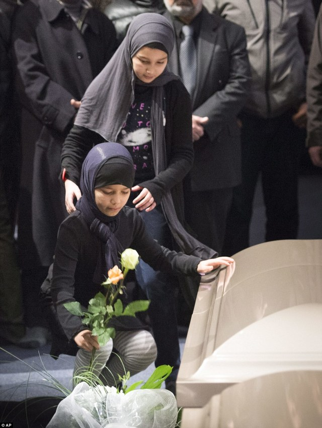 A young girl places a flower next to one of the caskets during a ceremony for three of the six victims of the Quebec City mosque shooting