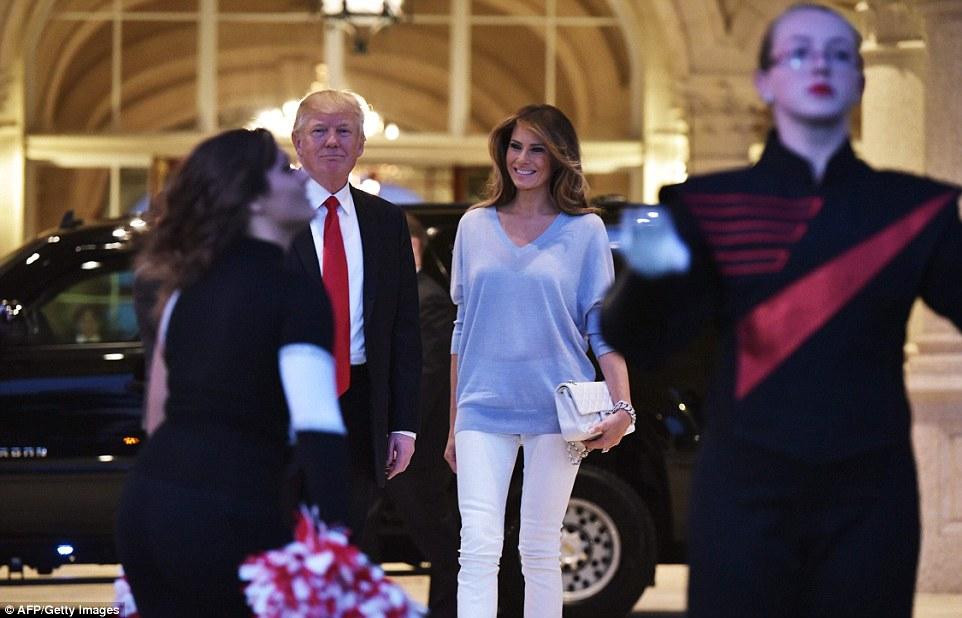 Olhar presidencial: Donald Trump e Primeira-dama Melania Trump assistir a banda Palm Beach Central High School executar como ele cumprimenta-los na chegada para assistir ao Super Bowl no Trump International Golf Club Palm Beach em West Palm Beach