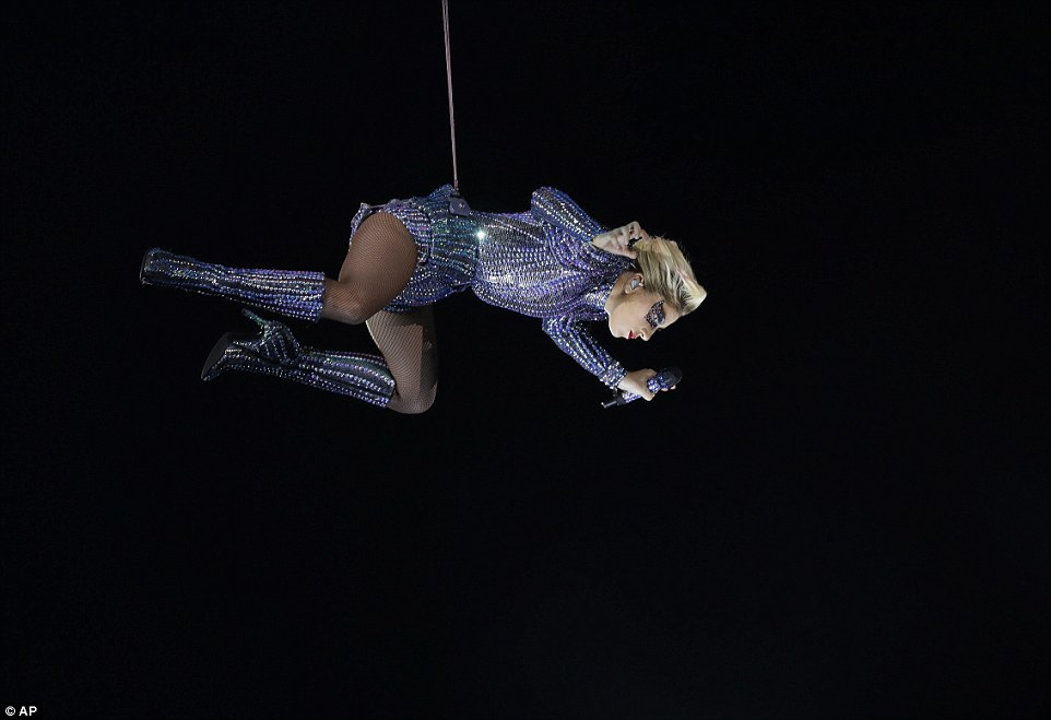 Flying through the air! the artist, 30, dangled high above the stadium crowd