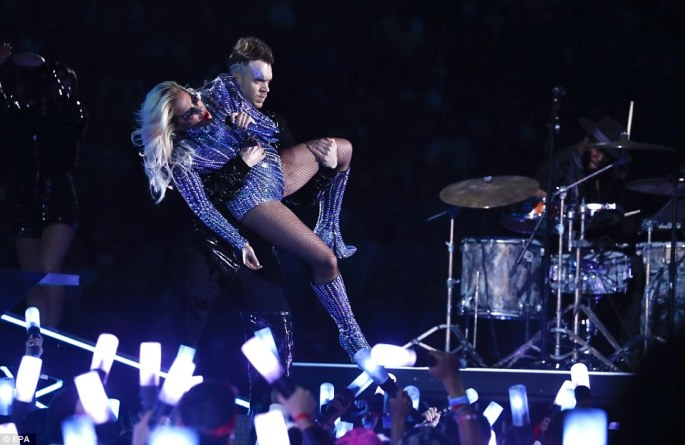 Acrobatic: Lady Gaga is helped by one of her backup dancers during her energetic half time show at the Super Bowl on Sunday