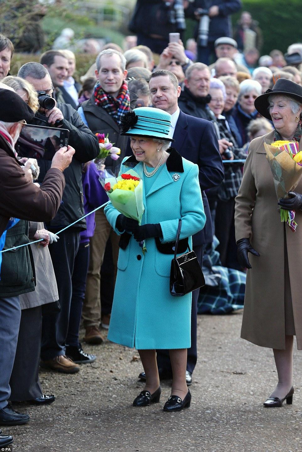 A rainha, que atualmente está em casa em Sandringham, parecia estar em espírito especialmente alto no domingo de manhã como ela chegou para um serviço de igreja em Norfolk.  Na foto: um aspirante a poço tira uma foto em seu tablet