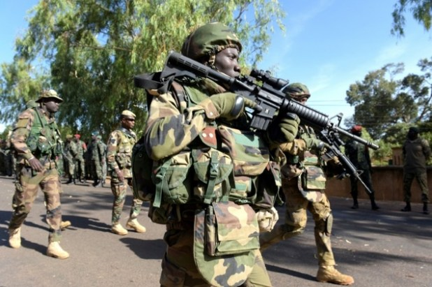 Soldiers from The Gambia and ECOWAS soldiers patrol in front of the Second Infantry Battalion Camp in Farafenni, Gambia on January 22, 2017