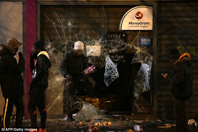 Crowds have also been pictured entering vandalised supermarkets and taking goods, pictured