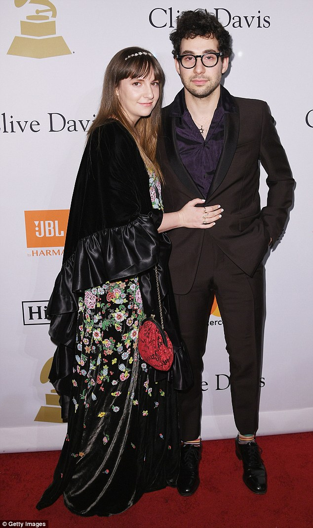 Celebrity couple: Dunham wore a black silky cape with a flounce hem and bell sleeves while her beau wore a black suit over a dark blue silk shirt and colorful stripy socks with black shoes