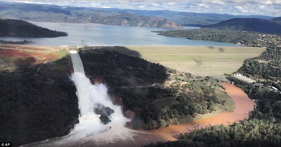 An image from video provided by the office of Assemblyman Brian Dahle shows water flowing over the emergency spillway