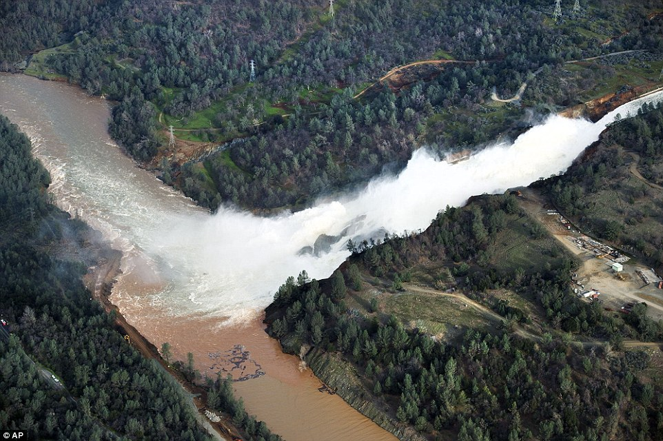 Still pouring:Water continues to run down the main spillway at Lake Oroville on Monday. The water level dropped overnight behind the nation's tallest dam