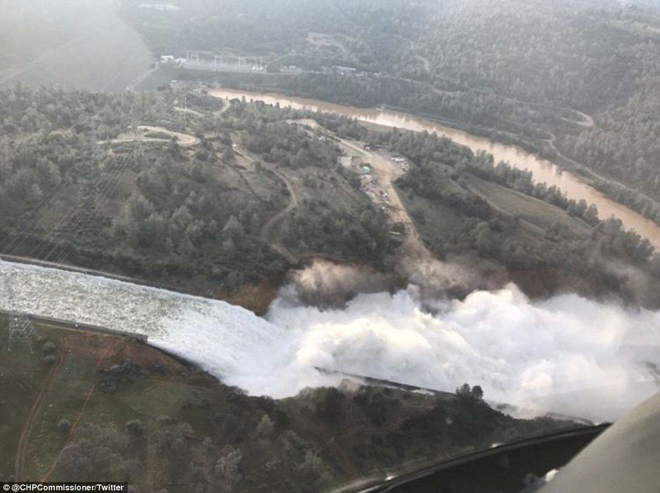 Still flowing: As the day began, officials from the California Department of Water Resources prepared to inspect an erosion scar (pictured) on the main spillway at the dam on Lake Oroville, about 150 miles northeast of San Francisco