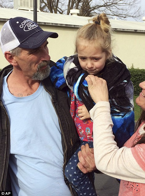 Waiting:Patrick Cumings, (left), holds his daughter, Elizabeth, and he stands with his wife, Elizabeth Cumings at the Red Cross evacuation center in Chico