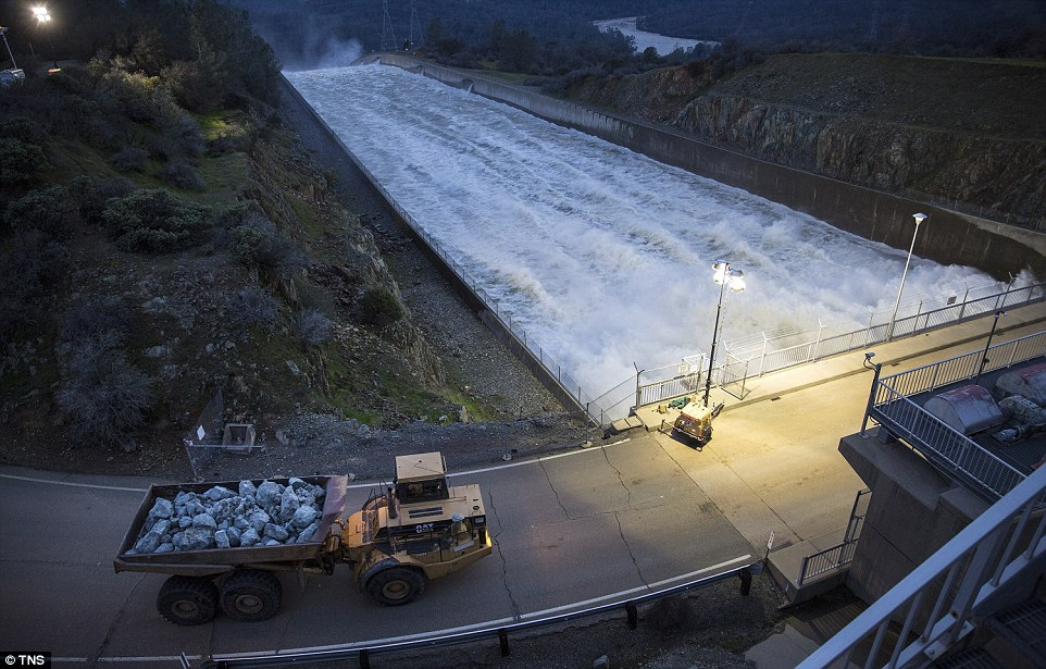 Delivery: A large truck full of rocks crosses the primary spillway on the way to deliver its cargo to the damaged emergency spillway at the dam on Monday