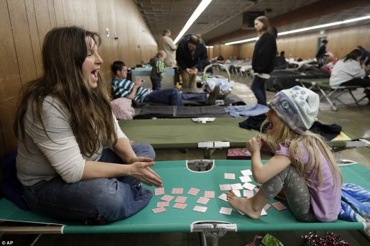 Among evacuees is Katherine Boeger Knight and her daughter Amethyst, five, who entertained themselves at a refuge in Chico, California, with cards on Monday night