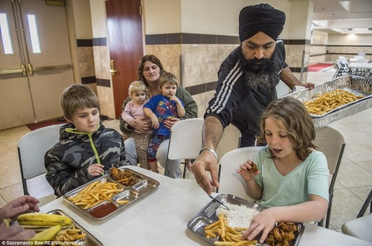 Sharing: At the Gurdwara Sahib Sikh Temple in Sacramento, Amarjit Singh dishes out french fries to the Lyon family who were forced to flee their home in Yuba City