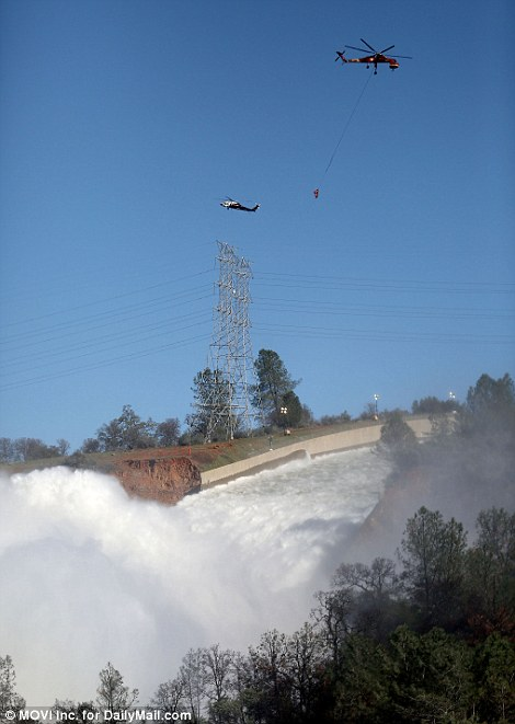 Helicopters fly rocks to the top of the dam for engineers to continue patching up the eroded emergency spillway (left) on Tuesday as water continues to cascade down the primary spillway right)