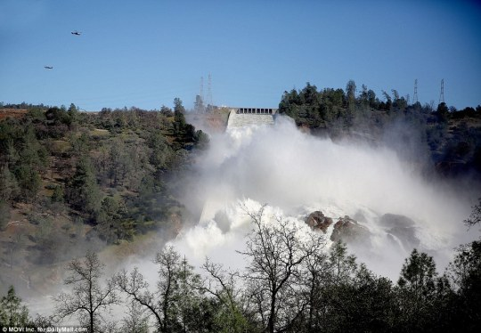 Helicopters fly over the emergency  spillway at Oroville Dam on Tuesday as millions of gallons of water rushes down its main chute