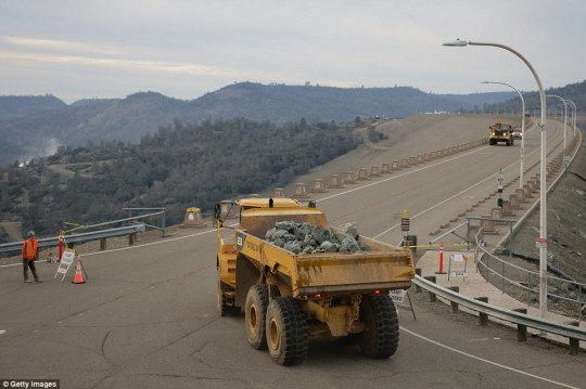 Engineers brought rocks to the top of the dam on Monday to lower patch up the damaged earthy emergency spillway