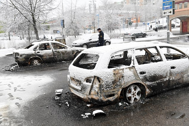 Intimidated: 'The youths come into my shop and threaten me and my staff almost every day,' said Nouri, 44, who runs a shoe shop near the train station where the riot erupted on Monday night. Pictured: The burned-out shells of cars which were set ablaze during the riot