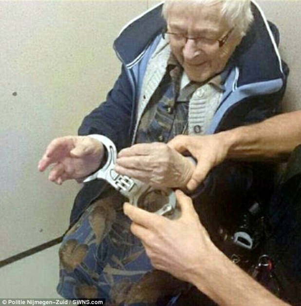 A police officer slips the 99-year-old's hands into the handcuffs at Nijmegen Zuid station