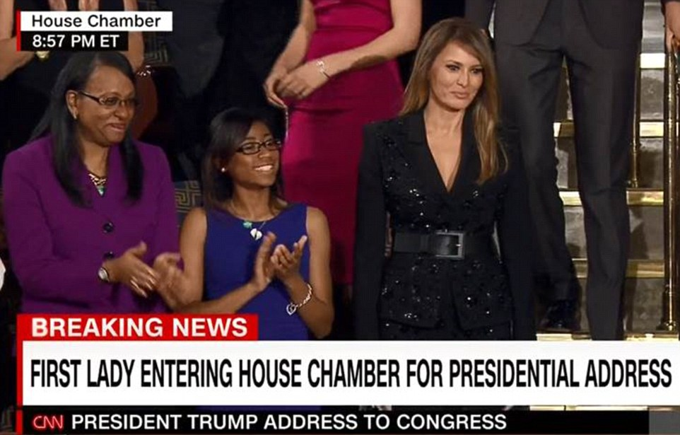Melania was wearing a sleek, sequinned Michael Kors black suit, pulled together with a wide black belt, as she listened to Trump speak