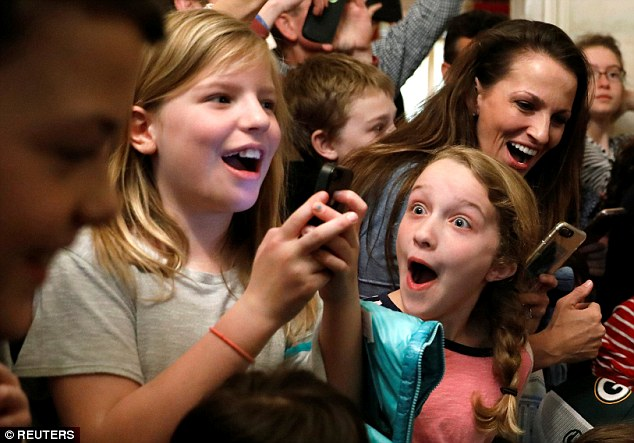 Two children react in shock and delight as they are surprised by the president during a tour of the White House