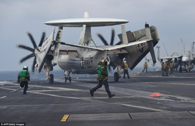 US Navy crew members run next to an E-2C Hawkeye as it lands on the deck of the USS Carl Vinson