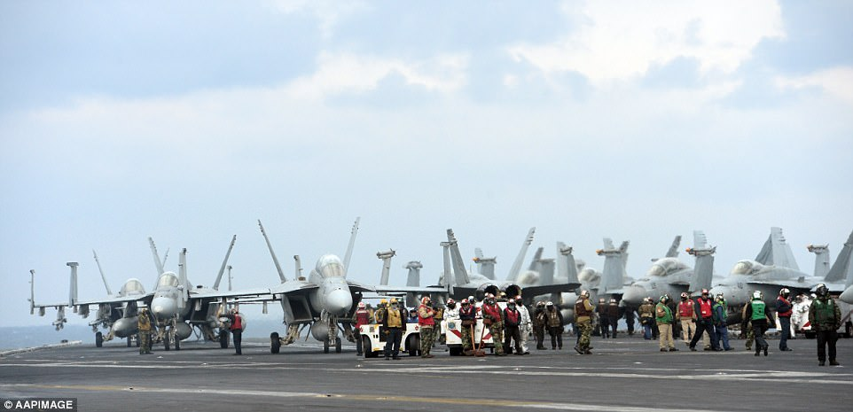 F/A Super Hornets and other fighter jets await takeoff aboard the nuclear-powered USS Carl Vinson aircraft carrier