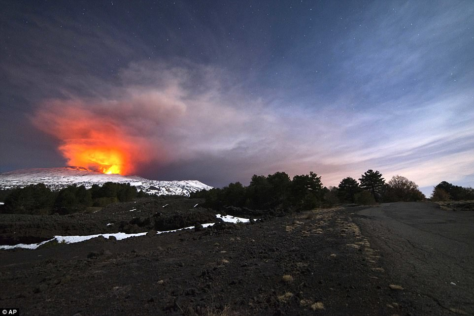Mount Etna is seen from the side of a road as it spews lava during an eruption earlier on Thursday