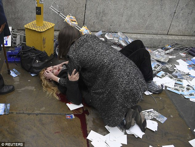 The 46-year-old mother desperately cluthced on to a stranger who held her bleeding head as she lay among scattered postcards while they waited for an ambulance. The chilling image swept the world yesterday before the pair were identified