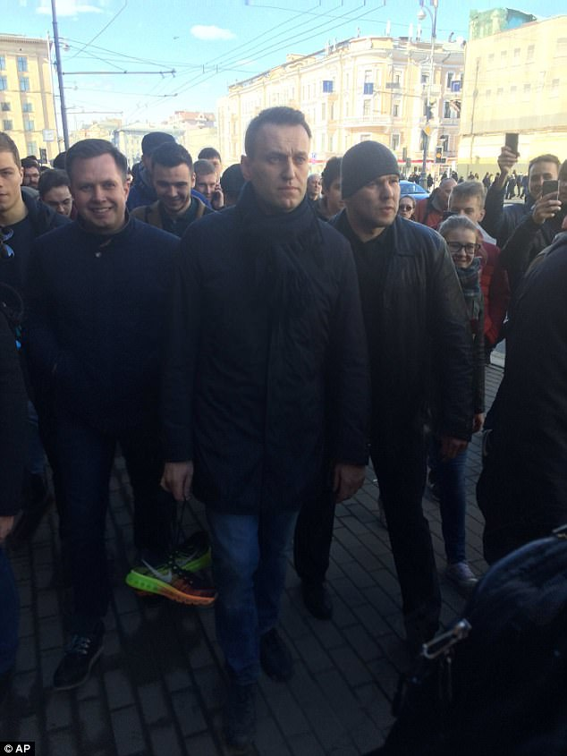Alexei Navalny, center, walks in downtown Moscow, Russia, Sunday, March 26, 2017