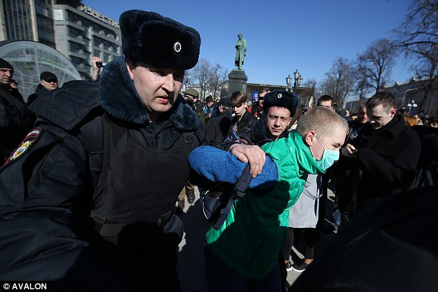 Police bundled Navalny into a minibus as he was walking to the protest. Pictured: An activist being led away